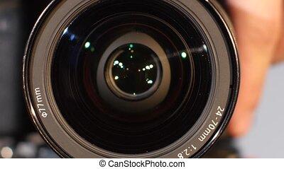 Camera lens, zoom, close up - Camera lens, hand shows the...