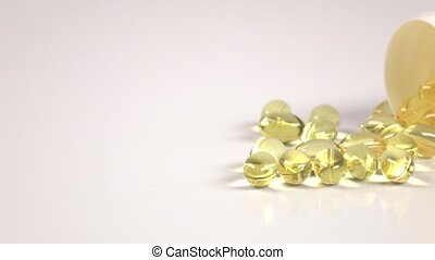 Fish fat oil capsules are scattered off of the medical jar...