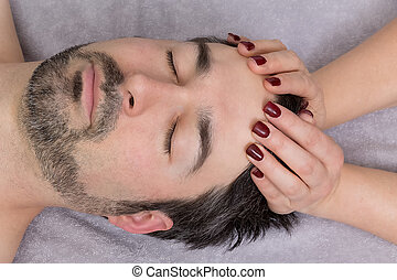 osteopathy - man in a treatment at the face