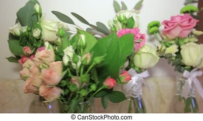 Bouquets with fresh flowers are in glass vases as decoration...