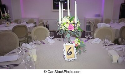 Tables setting with candles, cutlery for guests, decoration...
