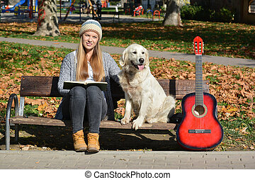 Girl, dog, book and guitar on a bench