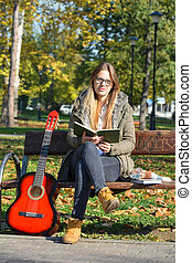 Girl, book and guitar on a bench