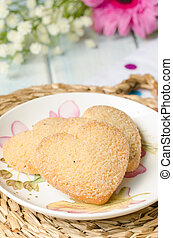 Heart-shaped butter cookies with sugar. - Plate with three...