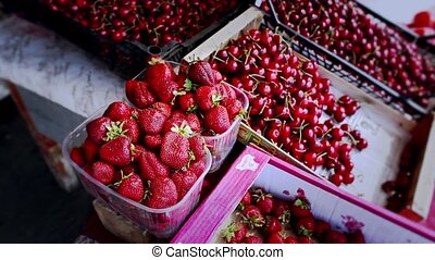 Small boxes full of fresh ripe strawberry and cherry -...