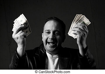 Man Celebrating with Cash - A man celebrating holding...