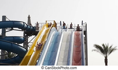 woman sliding down with joy in waterpark