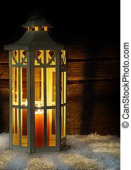 Lantern in the snow, wood background