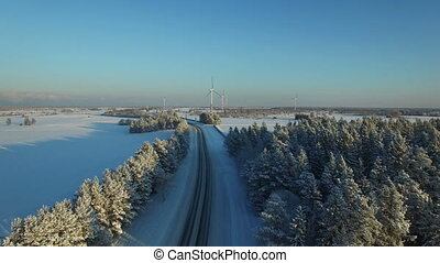 aerial view at the winter road with windmills.