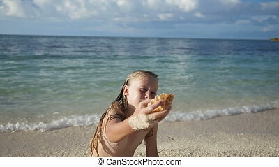 Child holding a seashell on the beach - Little girl holding...