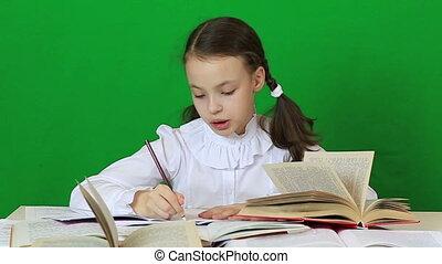 Little girl diligently doing their homework Green screen...