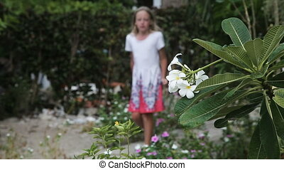 young girl smelling  flower on branch