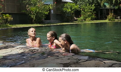 Happy family in the swimming pool - Mother and her two...