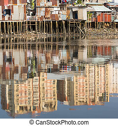 Views of the city's Slums from river. In water reflection of...