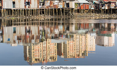 Views of the city's Slums from river - in water reflection...