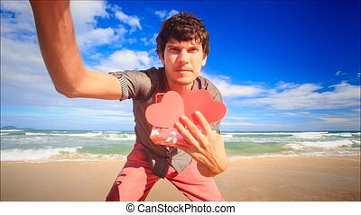Guy Shows to Camera Red Hearts Gift on Wave Surf Beach