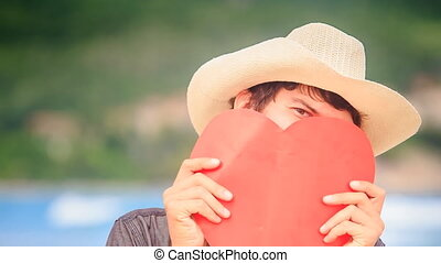 Guy in Hat Holds Red Heart in Front of Face Looks out in one Eye