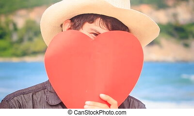 Guy in Hat Holds Red Heart in Front of Face Turns Head...