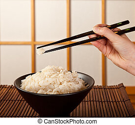 Rice bowl and chopsticks - Hands holding rice with...