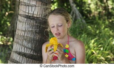 Young girl eating mango fruit
