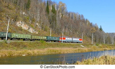freight train rides along the river in the Ural mountains in...