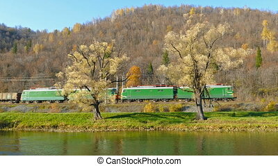 freight train rides along the river