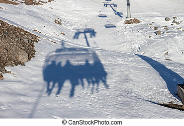 Silhoette of skiers on chairlift - Silhoette of skiers...