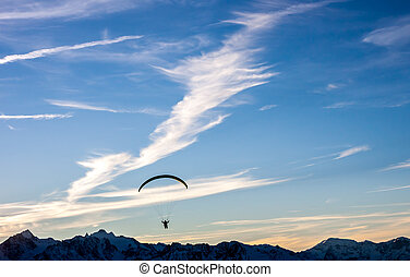 Silhouette of paraglide flying over mountains in front of...