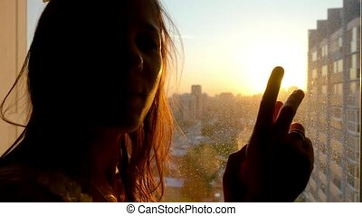 Girl touching the sunlight by hand in her room at home Happy...