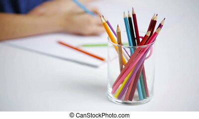 colour pencils in glass and girl drawing on paper - people,...