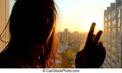 Girl touching the sunlight by hand in her room at home. Happy woman looking at shining sun through her fingers.