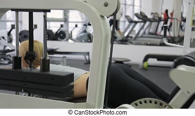 A athlete, blonde women with muscular body doing exercise on the buttocks and calves straining their muscles in the gym.