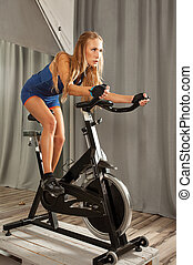 woman spinning gym - Young beautiful woman doing exercise on...