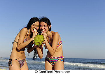 two young women drinking coconut water on the beach -...