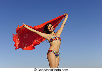 freedom: woman with beach towel against blue sky