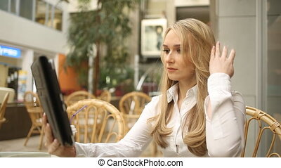 girl straightens her hair looking at a tablet computer. blond woman sitting in a cafe.