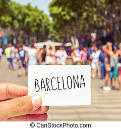 man at Las Ramblas shows a signboard with the word Barcelona...