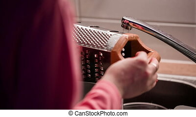 Young woman washes grater behind view. - Young woman washes...