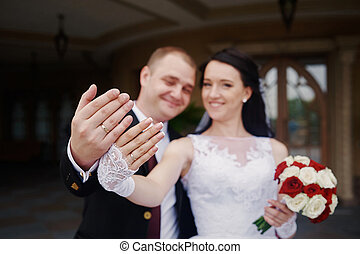 happy bride and groom showing their rings on hands
