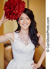 smiling bride holding a red flower on her head