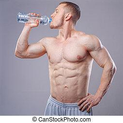 Athlete man drinking water over dark background