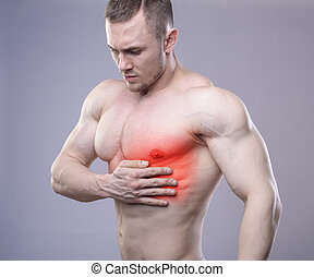 Athletic muscular man has pain in the heart Red spot of...