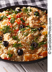 Couscous salad with chicken, olives and vegetables close-up...