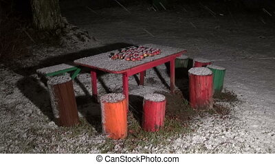 Snow falling on apples on table