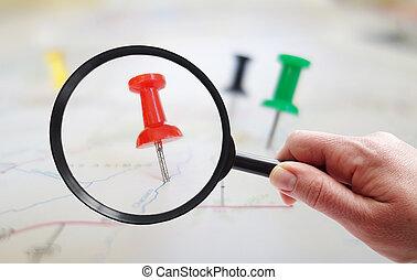 Map tacks closeup - Magnifying glass looking at closeup of...