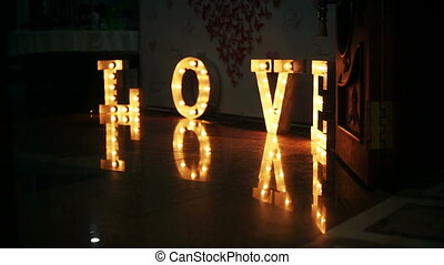 Word love consisting of lights on glossy floor