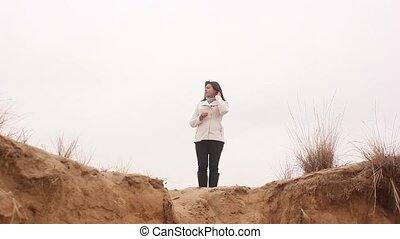 woman stands in the autumn on the nature of the sand cliff...