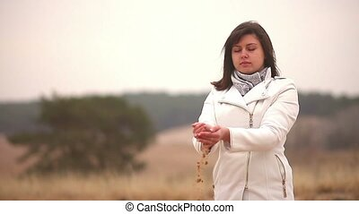 Woman throws sand symbol time autumn nature cold