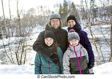 Happy parents and their kids in winterwear - Two Happy...