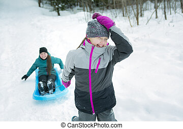 Children Pulling Sledge Through Snowy Landscape - Two...